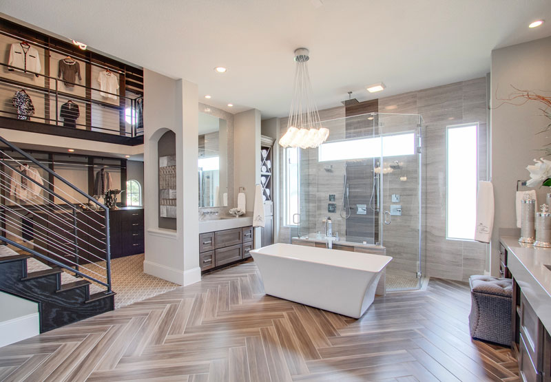 Frameless shower surround reveals contrasting marble plank tile detail and multiple jets in the shower. A spectacular chandelier floats above a soaking tub. Steel-framed cable stair parts lead to the two-story closet complete with custom cabinetry and storage.