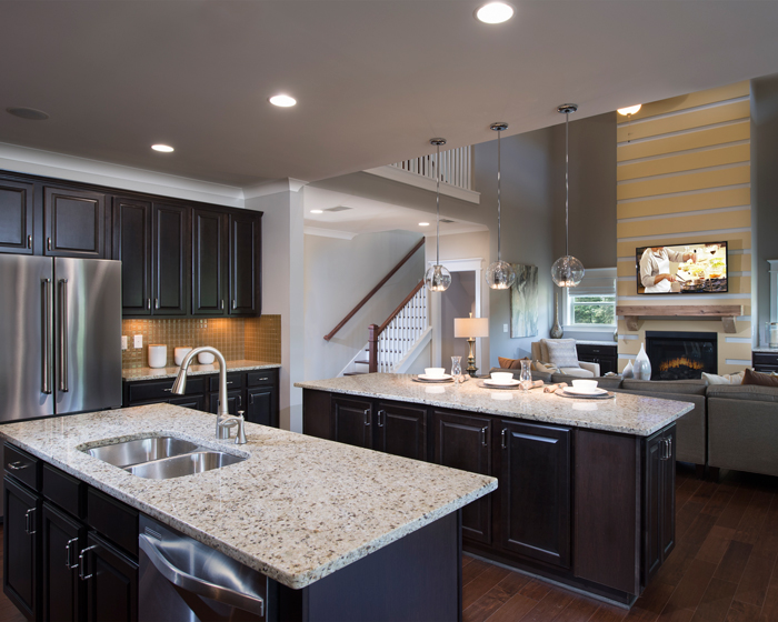 Another style of kitchen includes two islands and dark wooden cabinets. The open floorplan allows for a welcoming feeling.