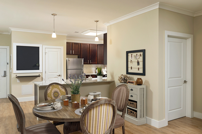 The modern kitchens include sleek espresso cabinetry, stainless steel appliances, and granite countertops.