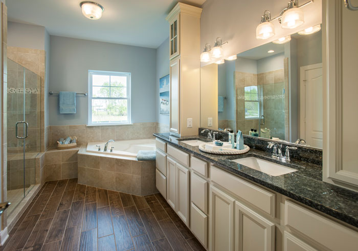 Wood tile in the master bath with a spacious tub and step-in shower, ontrasting countertop that houses dual-vanity sinks all create a functional space with ample natural light for a tranquil, spa-like experience.
