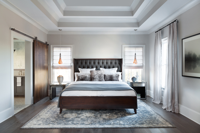 An opulent master suite includes chaises for resting or reading, with the bed dressed in soft, white bedding and fur accents.